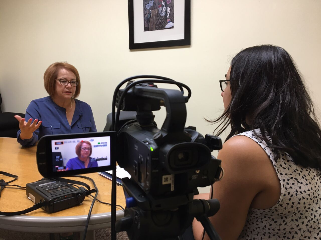 Analia Cabral interviews Maria Elena Durazo. Seated at table with video camera in foreground.