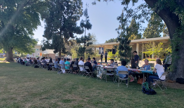 Students and community members sit together at long table on CSUF campus lawn