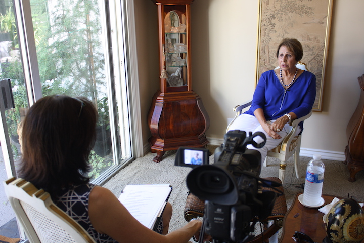Dr. Natalie Fousekis interviews Marilyn Brewer in her home with video camera in foreground.
