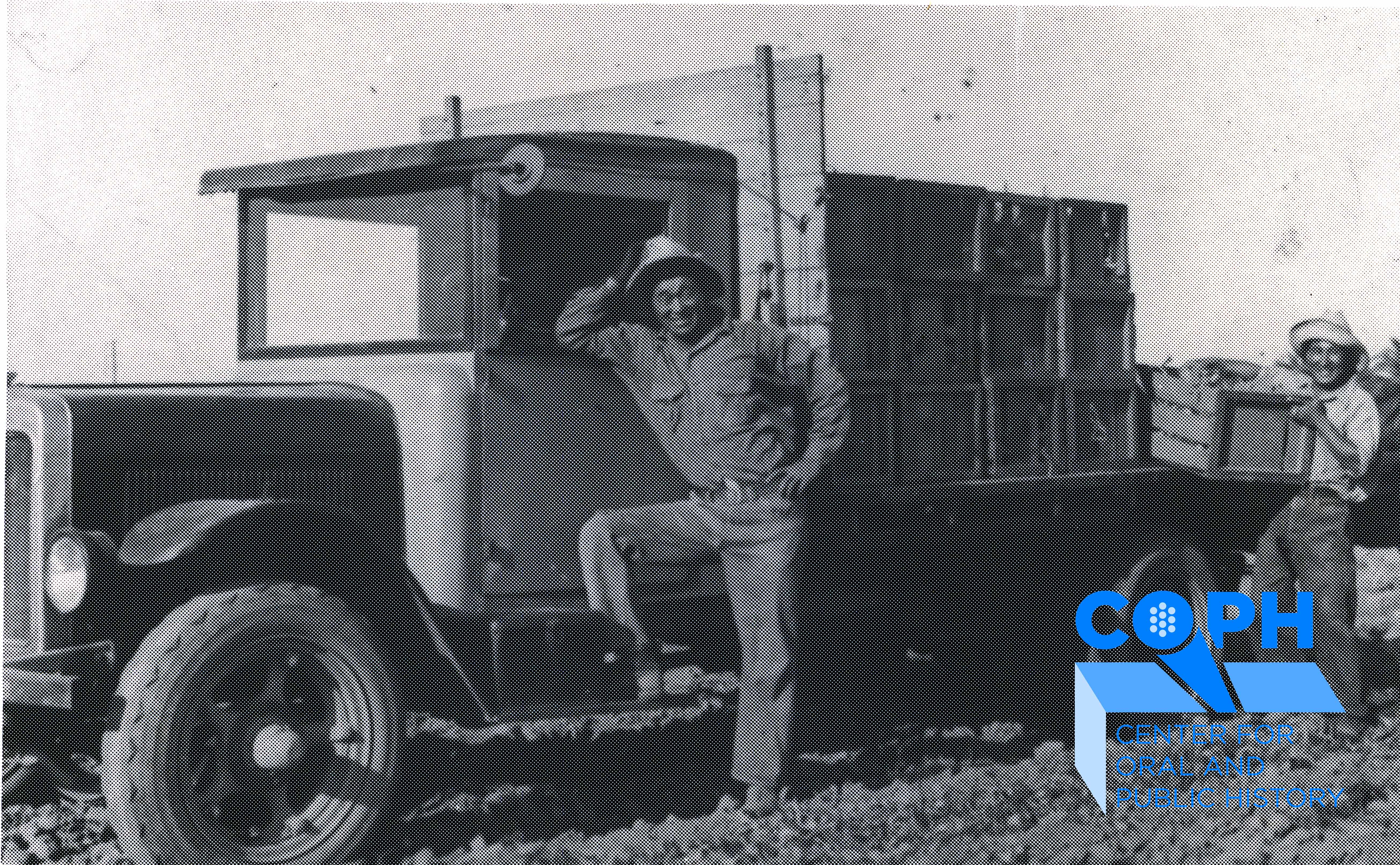 Clarence Nishizu stands in front of truck with produce in field