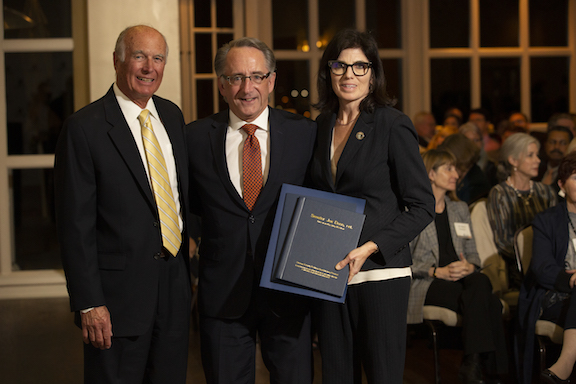 Dick Ackerman, Joe Dunn, and Natalie Fousekis stand posed for a picture inside the Summit House restaurant at the OC Politics event